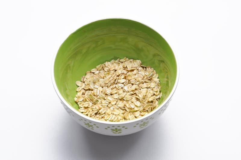 Gesundes Frühstück Korn in gree Schüssel lokalisiert auf weißem Hintergrund lizenzfreies stockbild