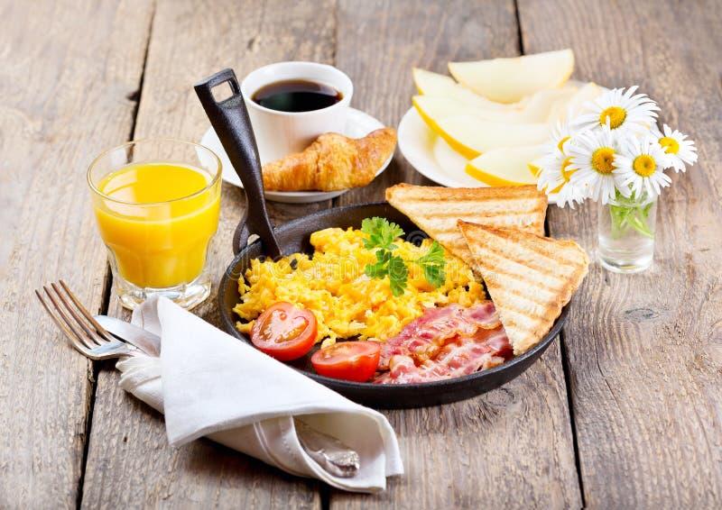 Gesundes Frühstück mit durcheinandergemischten Eiern, Saft und Früchten lizenzfreies stockbild
