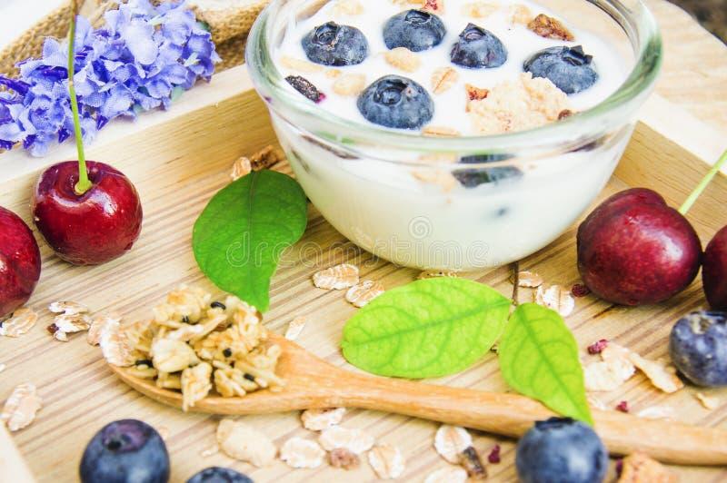 Gesundes Frühstück mit frischem Jogurt, Granola und muesli mit Kirsche und Beeren im kleinen Glas auf hölzernem Behälter, Nahrung lizenzfreie stockfotografie