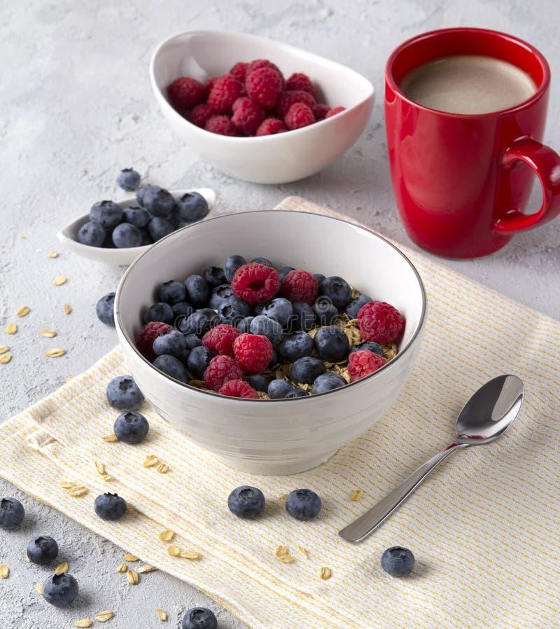Gesundes Frühstück mit Hafermehl, Kaffee und Beeren lizenzfreie stockbilder