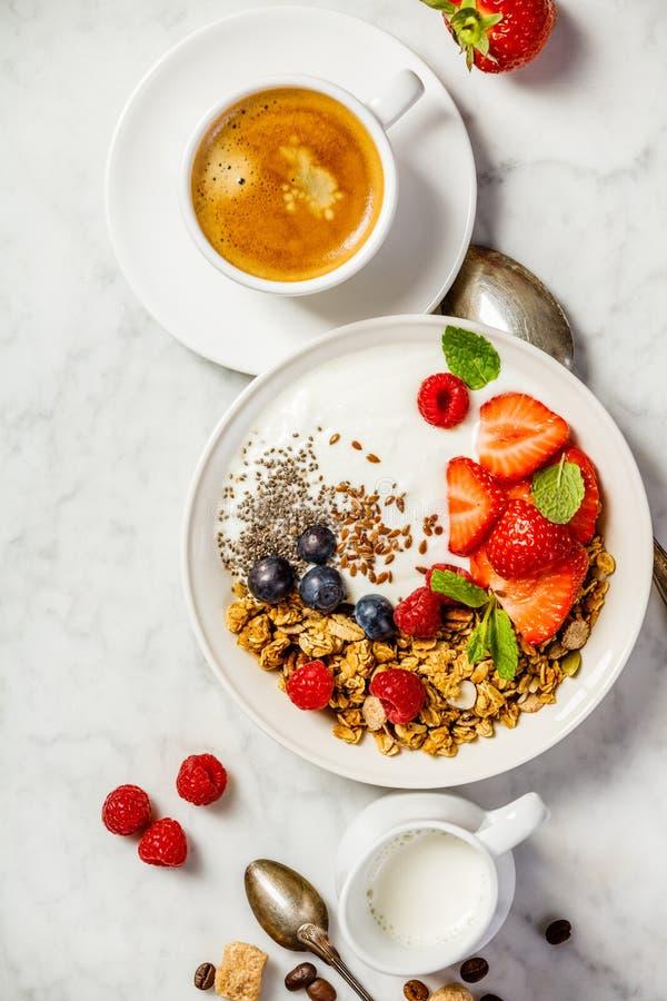 Gesundes Frühstück mit Kaffee, Jogurt, Granola und Beeren lizenzfreie stockfotografie