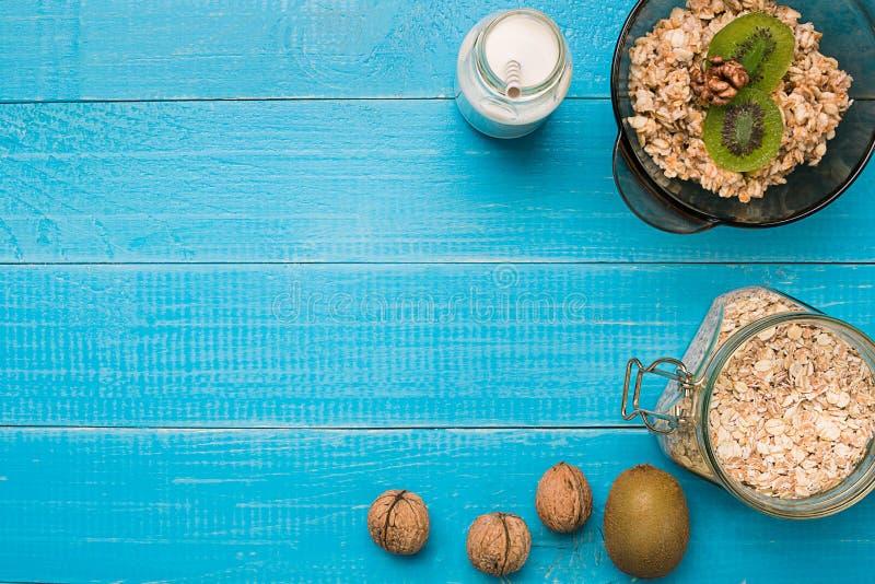 Gesundes Frühstück mit Schüssel des selbst gemachten Hafermehls mit Früchten und Milch über rustikalem hölzernem Hintergrund lizenzfreies stockfoto