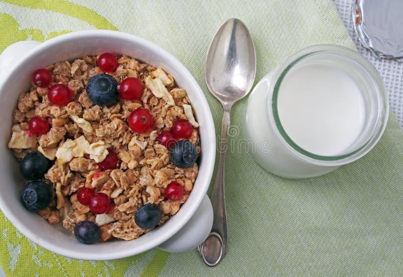 Gesundes Frühstück muesli mit Blaubeere und rote Johannisbeere und Milch mit Blaubeere und Himbeere stockfotografie