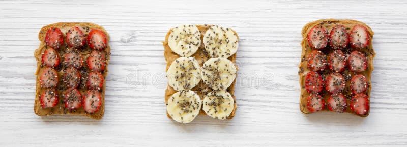 Gesundes Frühstück, nährendes Konzept Toast des strengen Vegetariers mit Erdnussbutter, Früchten und chia Samen über weißer Holzo lizenzfreie stockfotografie