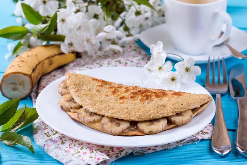 Gesundes Frühstück - Pfannkuchen vom Hafermehl mit Banane auf einem hölzernen Hintergrund lizenzfreie stockbilder