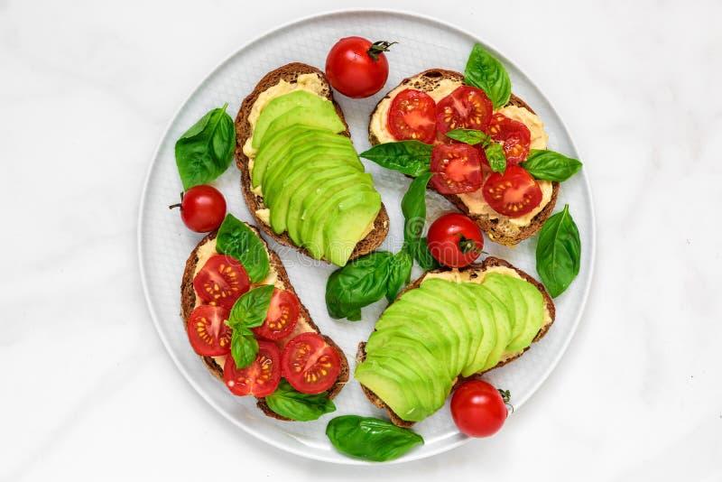 Gesundes Frühstück röstet mit Avocado, Tomaten, hummus und Basilikum über weißer Marmortabelle lizenzfreies stockfoto