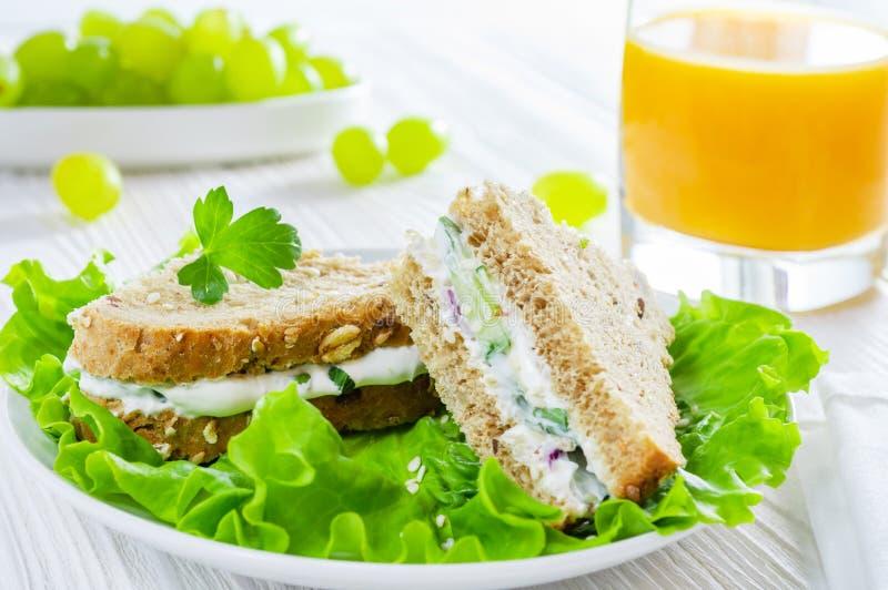 Gesundes Frühstück: Sandwiche mit Gemüse und Kräuter, Orangensaft und Trauben auf weißem Holztisch stockbild