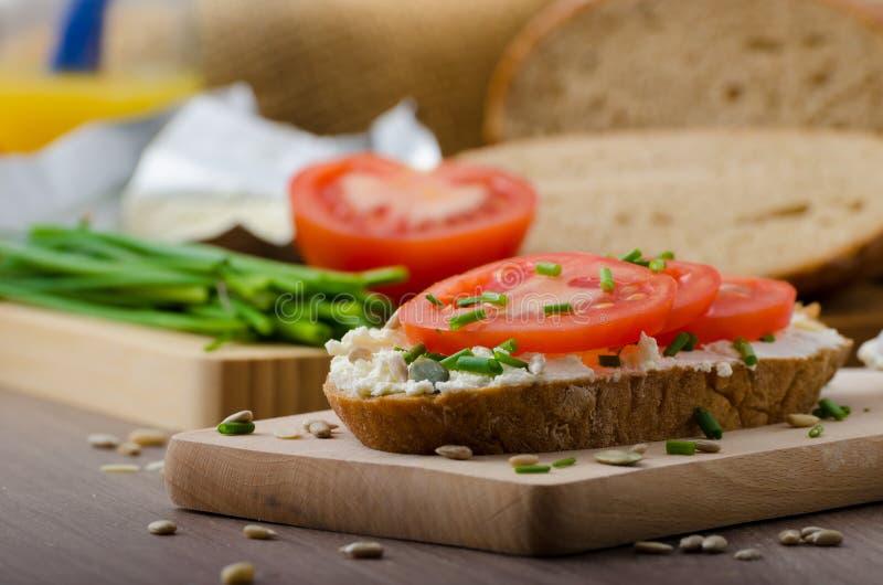 Gesundes Frühstück - selbst gemachtes Bierbrot mit Käse, Tomaten stockbild
