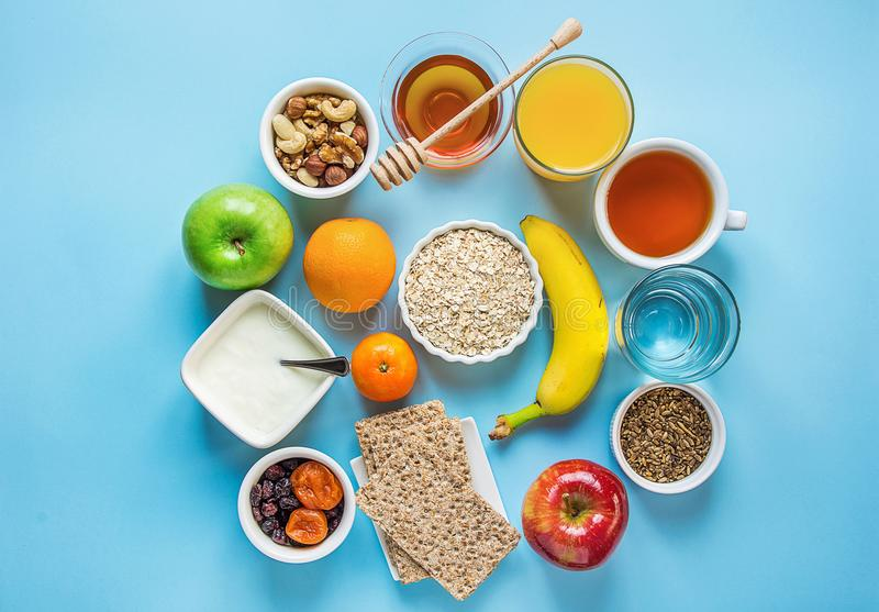 Gesundes Frühstücks-Faser-Quellverdauungs-Hafermehl Honey Fruits Apples Banana Orange Juice Water Green Tea Nuts Hellblaue Tabell stockbilder