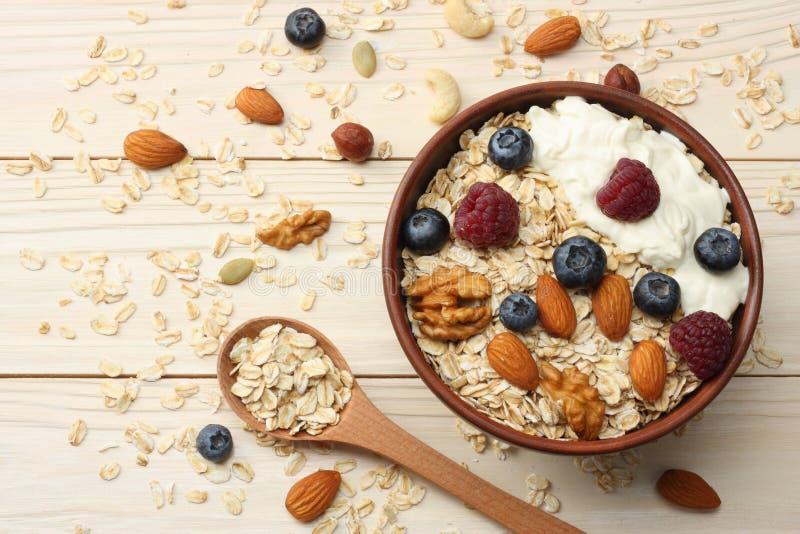 gesundes Frühstückshafermehl, -blaubeeren, -himbeeren und -nüsse auf weißem Holztisch Draufsicht mit Kopienraum lizenzfreie stockfotos