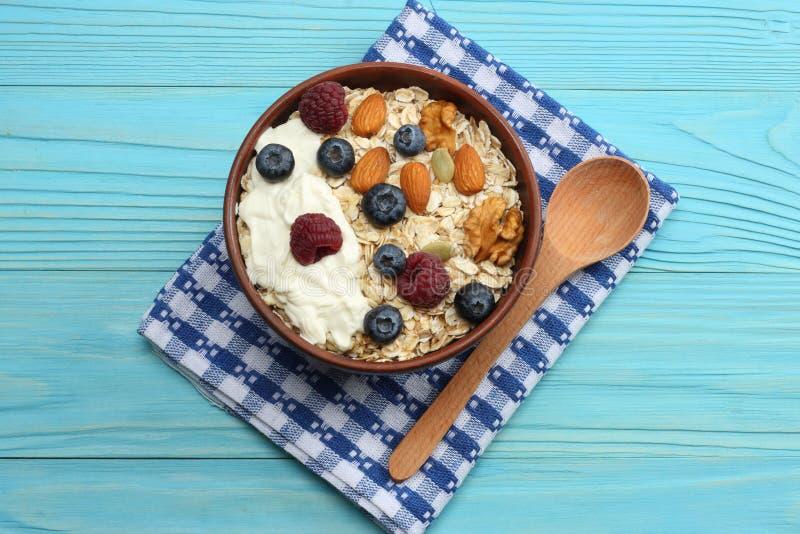 gesundes Frühstückshafermehl, -honig, -blaubeeren, -himbeeren und -nüsse auf blauem Holztisch Draufsicht mit Kopienraum lizenzfreies stockfoto