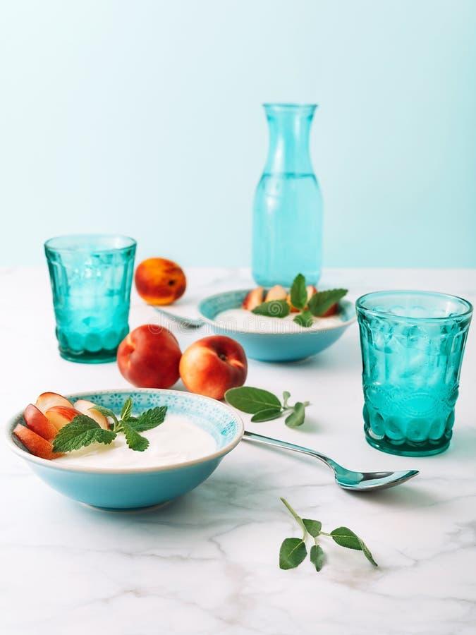 Gesundes Frühstückskonzept des natürlichen griechischen Joghurts, der Frucht und des Wassers auf Marmortabelle stockbild