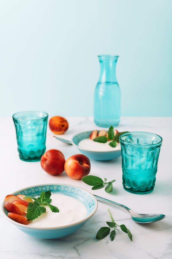 Gesundes Frühstückskonzept des natürlichen griechischen Joghurts, der Frucht und des Wassers auf Marmortabelle stockfotos