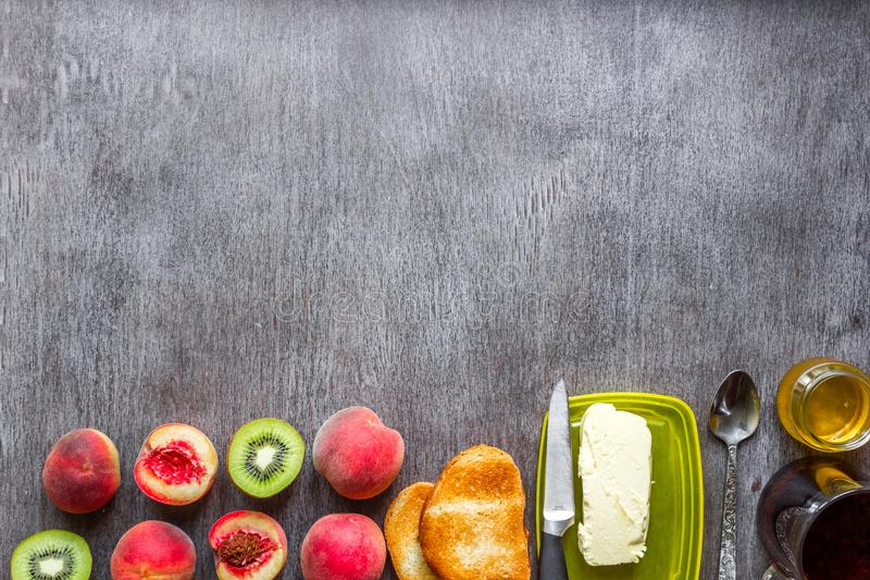 gesundes Frühstückskonzept Toast mit Butter, Honig, Früchten und Tee über dunklem hölzernem Hintergrund stockfoto