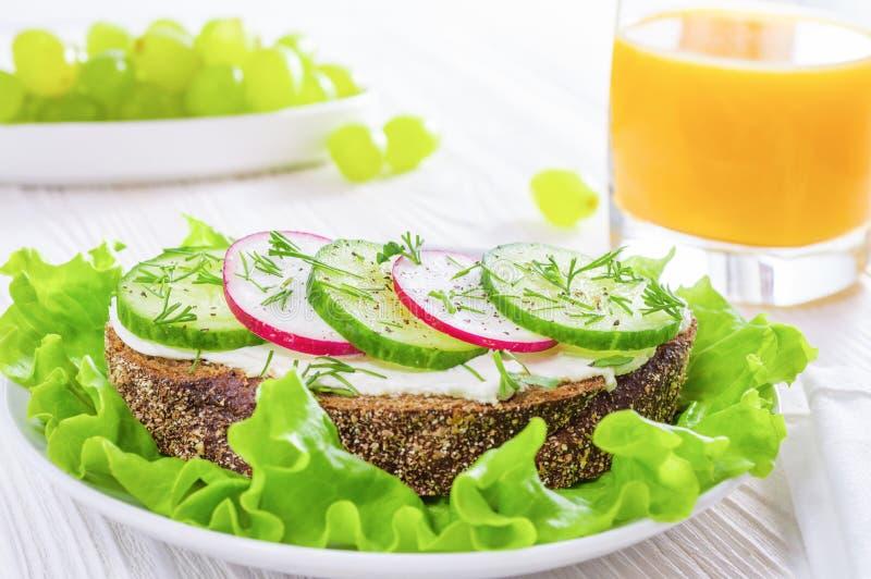 Gesundes Fr?hst?ck: Sandwiche mit Gem?se und Kr?uter, Orangensaft und Trauben auf wei?em Holztisch stockfotos