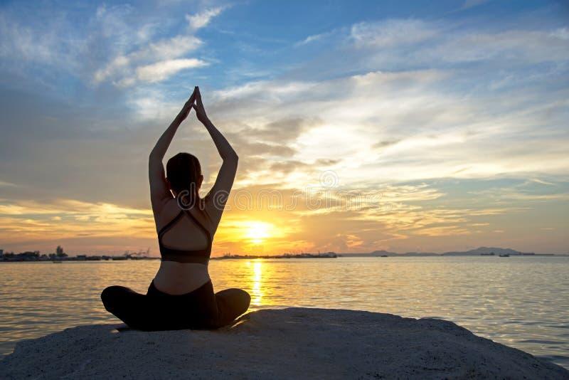 Gesundes gutes Meditationsyogalebensstil-Frauenschattenbild auf dem Seesonnenuntergang, entspannen sich wesentliches stockbild