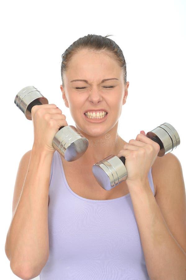 Gesundes junge Frauen-Training mit stummen Bell-Gewichten, die belastet schauen stockfoto