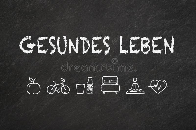 `Gesundes Leben` text and icons on a blackboard. Translation `Healthy life` royalty free illustration