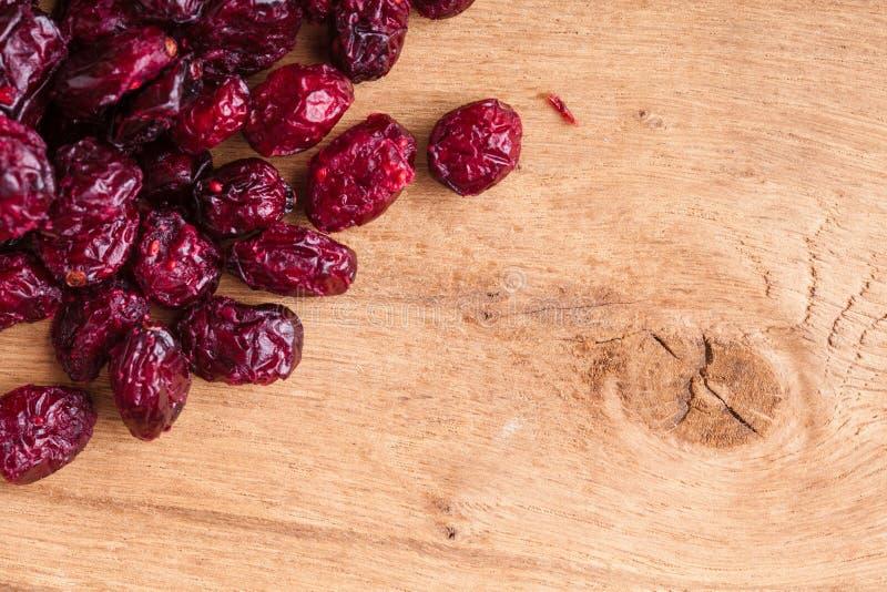Gesundes Lebensmittel der Diät. Grenze von getrockneten Moosbeeren auf hölzernem Hintergrund lizenzfreie stockfotografie