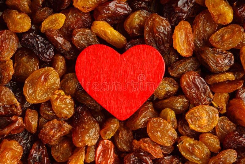 Gesundes Lebensmittel der Diät. Rosine als Hintergrundbeschaffenheit und rotes Herz lizenzfreie stockfotografie