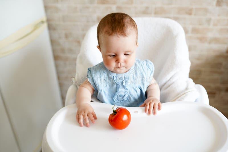 Gesundes Lebensmittel f?r Kinder Entz?ckendes kleines Baby, das in ihrem Stuhl sitzt und mit Gem?se spielt kleines M?dchen essen  lizenzfreies stockfoto
