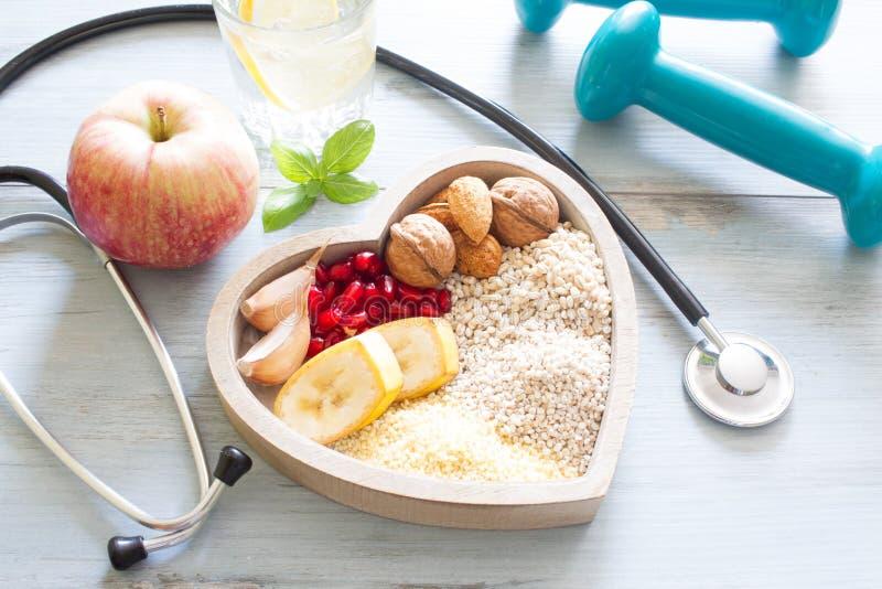 Gesundes Lebensmittel im Herzen und Wasser nährt Sportkonzept lizenzfreie stockbilder