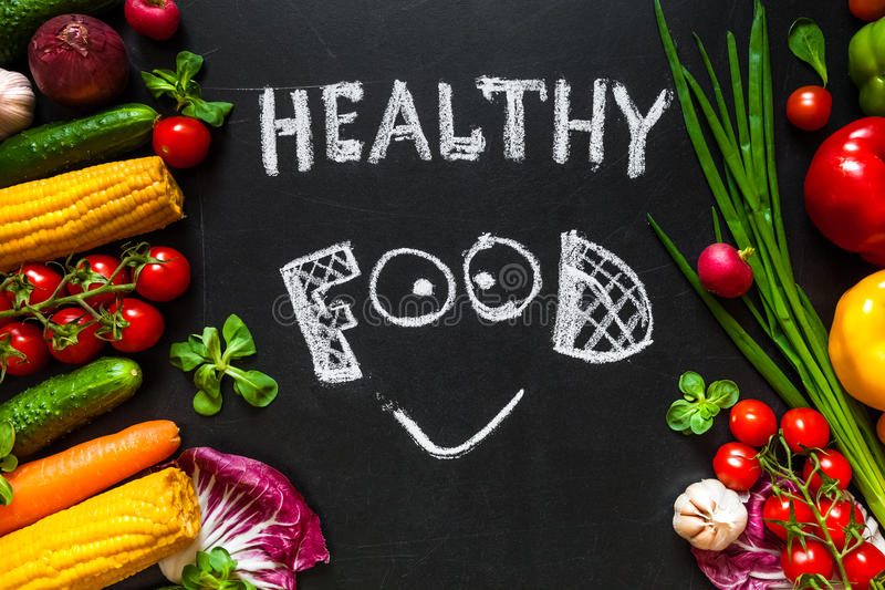 Gesundes Lebensmittelkonzept mit Frischgemüse für das Kochen Titel ` wird gesundes Lebensmittel ` mit Lächeln durch Kreide auf de stockfotos