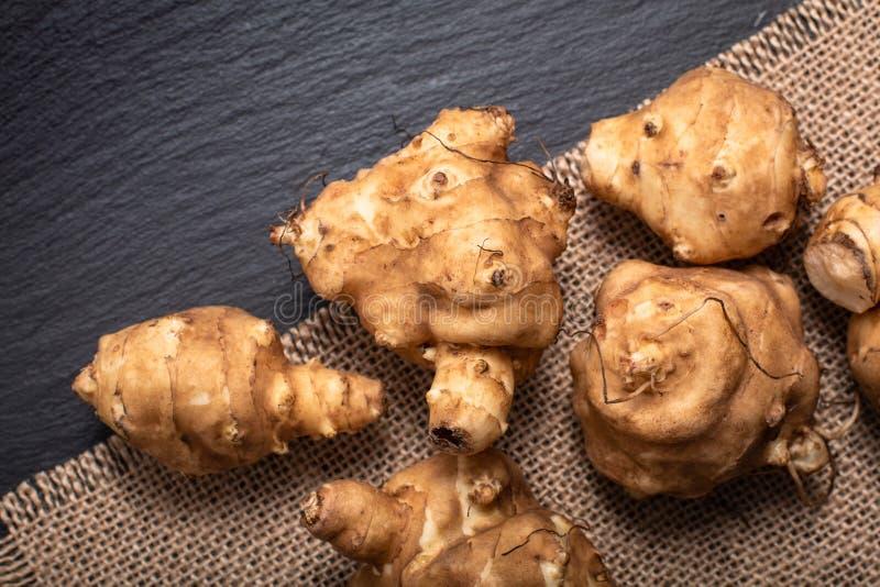 Gesundes Lebensmittelkonzept organisches Topinambur auf schwarzem Schiefer stockfotografie