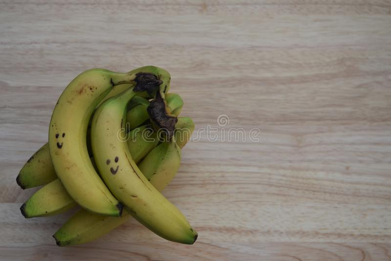 Gesundes Lebensmittelphotographiebild mit frischer Frucht von Bananen mit gezogenem auf glücklichem Lächeln auf rustikalem hölzer lizenzfreie stockfotos