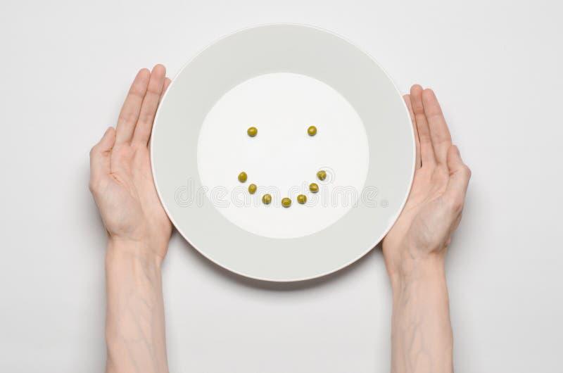 Gesundes Lebensmittelthema: Hände, die eine Platte von grünen Erbsen auf einer weißen Tischplatteansicht halten stockfoto