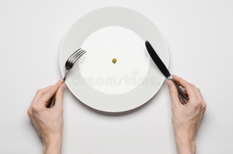 Gesundes Lebensmittelthema: Hände, die Messer und Gabel auf einer Platte mit grünen Erbsen auf einer weißen Tischplatteansicht ha stockfotos