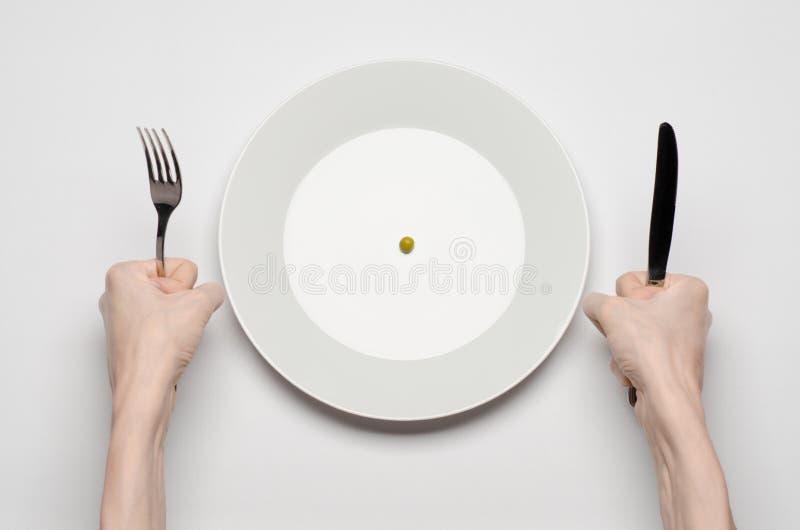 Gesundes Lebensmittelthema: Hände, die Messer und Gabel auf einer Platte mit grünen Erbsen auf einer weißen Tischplatteansicht ha lizenzfreies stockbild