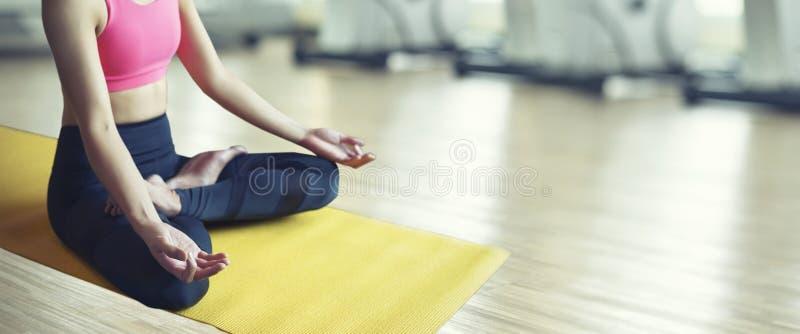 Gesundes Lebensstilkonzept Die Frauen, die Handübende Yogahaltung sitzen, meditiert im Lotussitz an der Yogaklasse stockbild