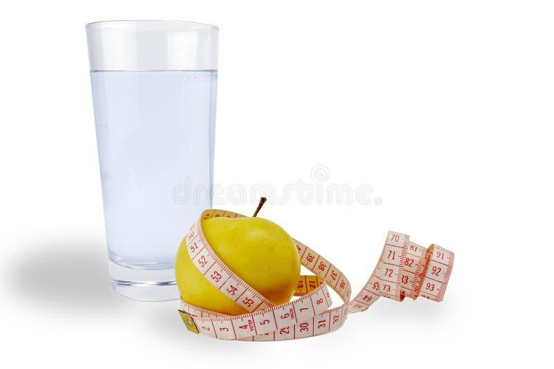 Gesundes Lebensstilkonzept Ein Apfel, ein messendes Band, ein Glas Wasser auf einem weißen Hintergrund, Isolat lizenzfreie stockfotos