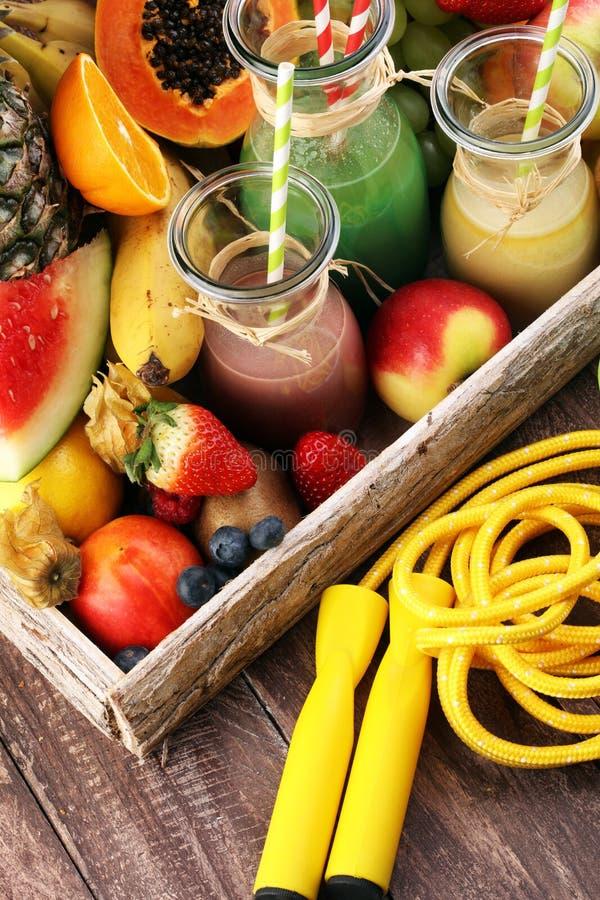 Gesundes Lebensstilkonzept tragen Sie Eignung Ausrüstung-einige Flaschen mit den Frucht- und Beerensaftsmoothies und -milchshaken stockfotos