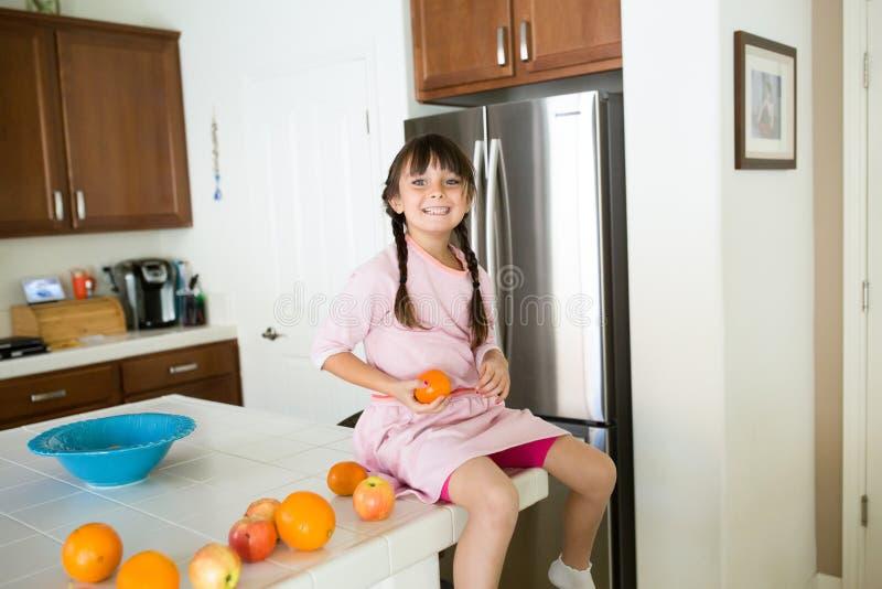 Gesundes Mädchen in der Küche mit Früchten lizenzfreies stockbild