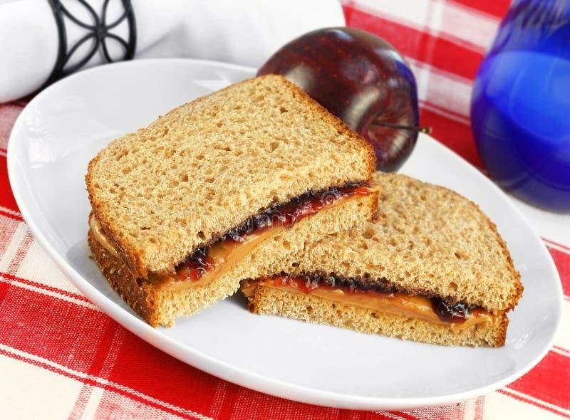 Gesundes Mittagessen der Erdnussbutter und der Jelly Sandwichs auf Vollweizen lizenzfreie stockfotos