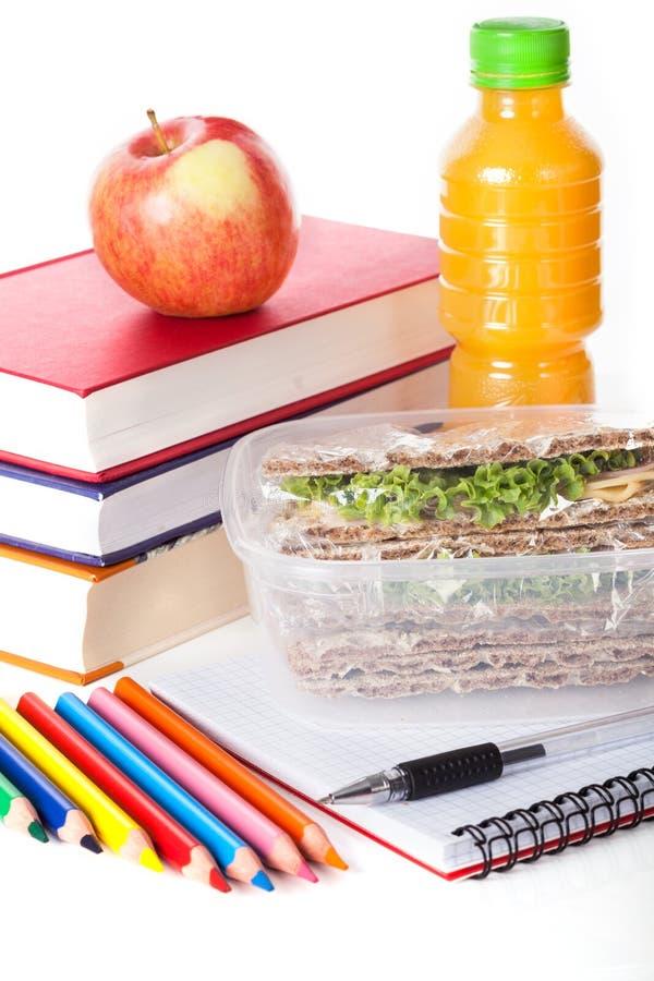 Gesundes Mittagessen mit Schulbedarf lizenzfreie stockbilder