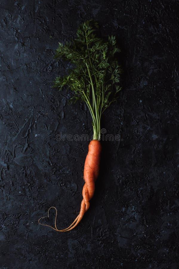 Gesundes Nahrungsmittelkonzept Frische organische Karotte mit Herzform auf Draufsicht des schwarzen Hintergrundes stockbilder