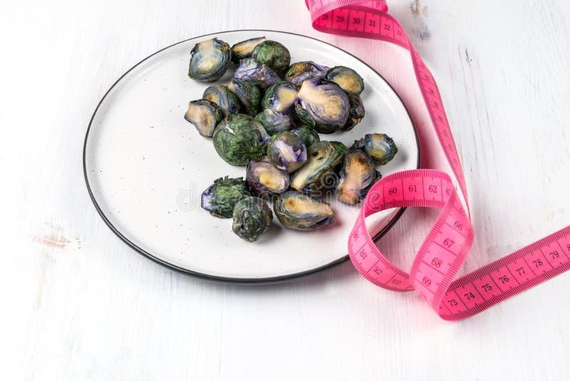 Gesundes Nahrungsmittelkonzept, Nähren, vegetarisch, strenger Vegetarier - organischer purpurroter Rosenkohl gebraten auf Platte  stockbilder