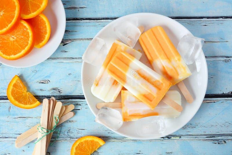 Gesundes orange Jogurteis am stiel, Draufsichttabellenszene gegen Purpleheart stockfotografie