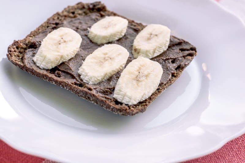 Gesundes Roggenbrot mit Johannisbrotbaum und Banane auf der weißen Platte Gesundes Konzept lizenzfreies stockfoto