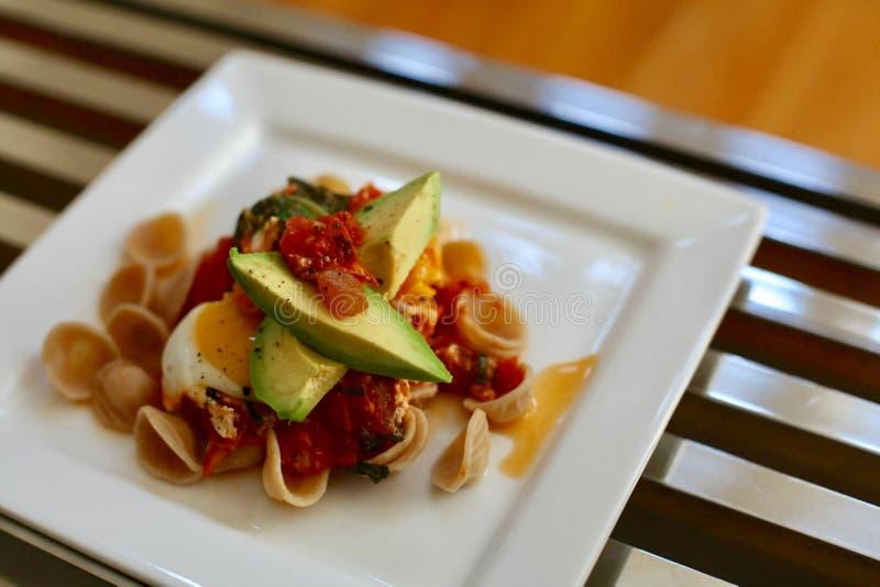 Gesundes Teigwaren-Abendessen mit Tomate und Avocado stockfotografie