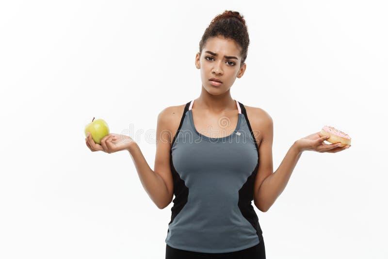 Gesundes und Diätkonzept - schöner sportlicher Afroamerikaner treffen eine Entscheidung zwischen Donut und grünem Apfel ein getre stockfotografie