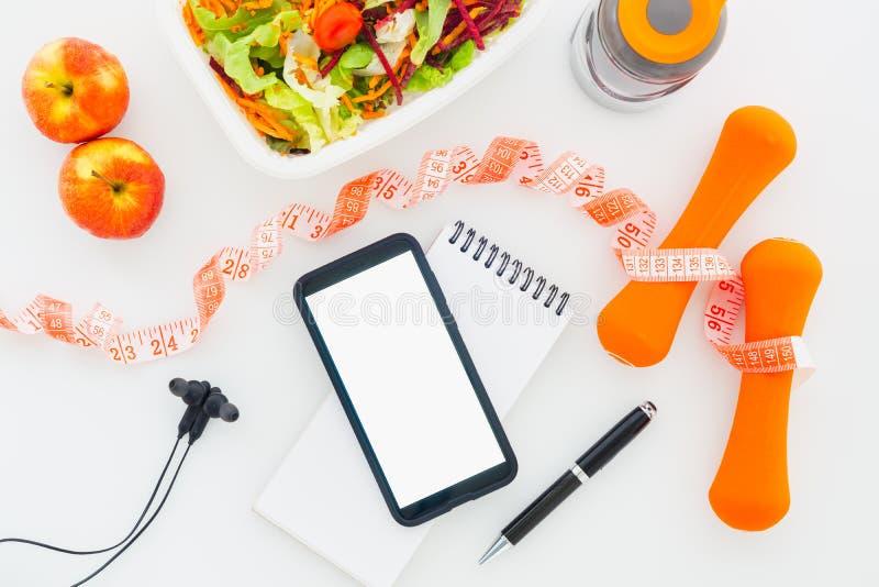 Gesundes und nährendes Planmodell der Eignung auf Tablette mit Handy des leeren Bildschirms für Modell, Kopfhörer, Flasche Wasser lizenzfreies stockbild