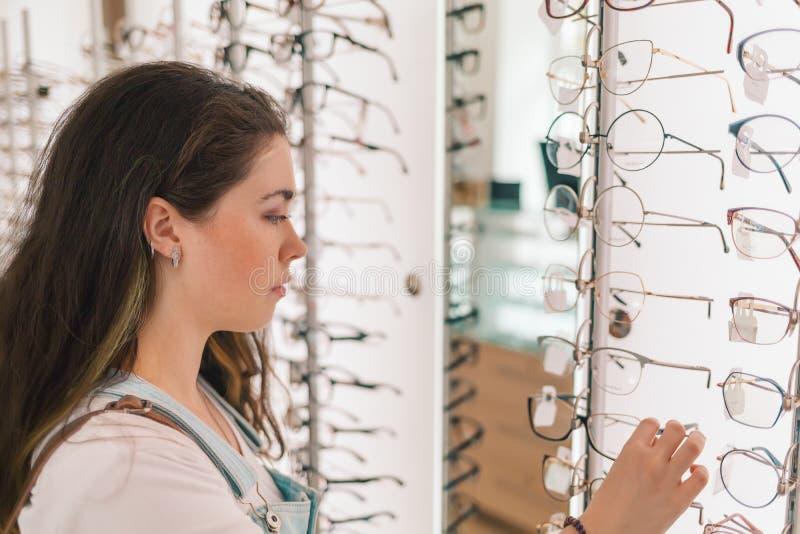 Gesundheit und Vision Eine junge und hübsche Frau wählt Gläser im Salon von Optik lizenzfreie stockfotografie