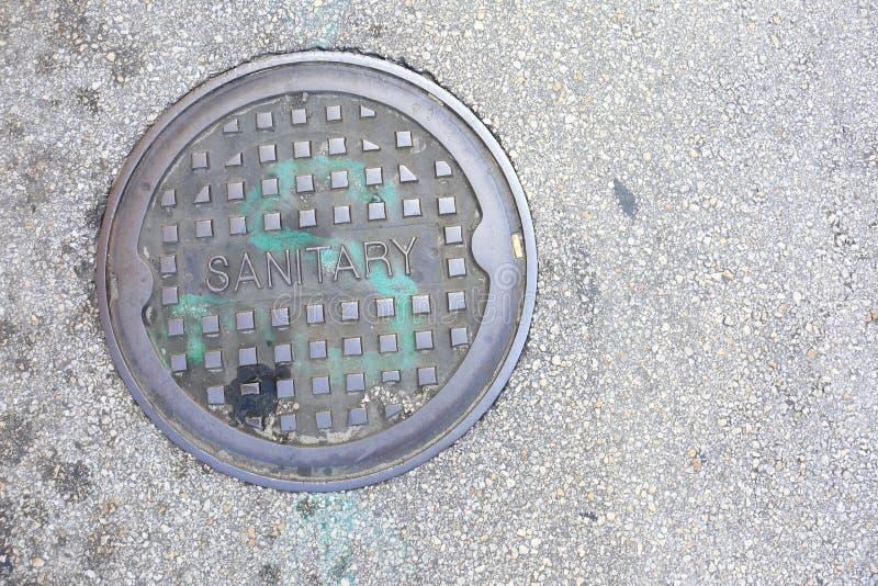 Gesundheitlicher StahlKanaldeckel auf Asphalt City Street stockfotos