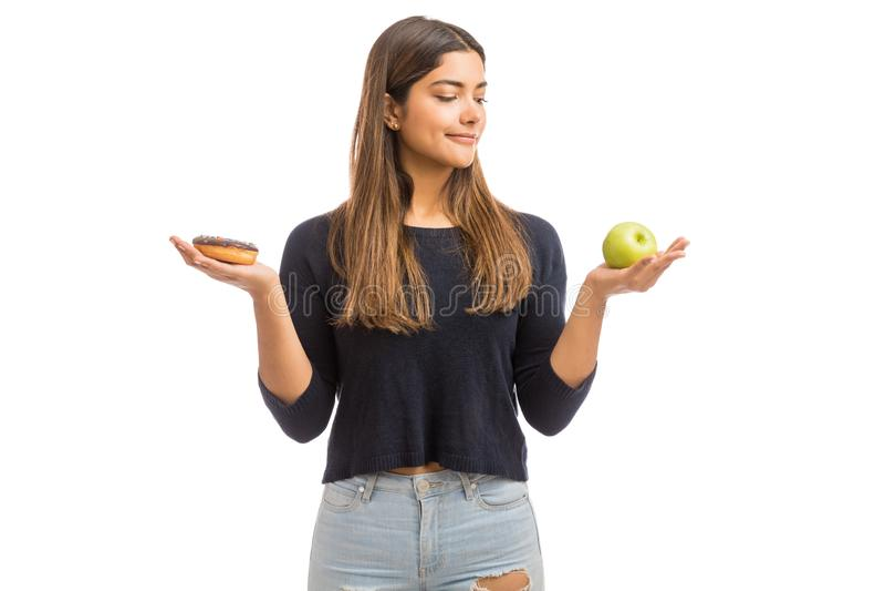 Gesundheits-bewusste Frau, die zwischen Apple und Donut vorwählt stockfoto