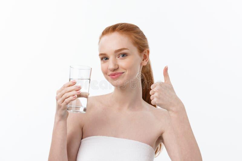 Gesundheits-, Leute-, Nahrungsmittel-, Sport-, Lebensstil- und Schönheitsinhalt - lächelnde junge Frau mit Glas Wasser stockfotografie