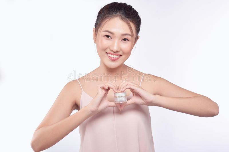 Gesundheits- und Sch?nheitskonzept - attraktive asiatische Frau, die Creme auf ihrer Haut auftr?gt lizenzfreie stockbilder